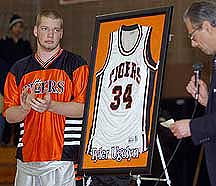 Ridgefield High School basketball player Daryl Yankowski, left, watches school Principal Ralph Ellis retire the jersey of former player and World Trade Center victim Tyler Ugolyn.
